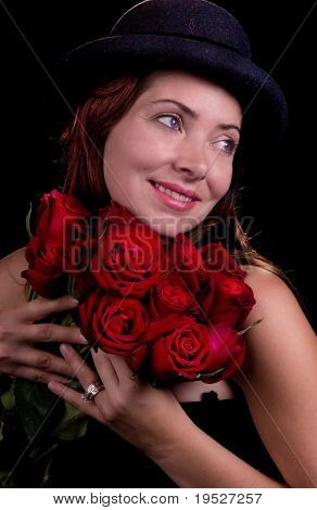 close-up of smiling woman in bowler hat holding 12 red roses