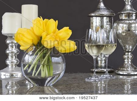 yellow tulips in vase with glasses of wine & home decor accessories - elegant tablescape