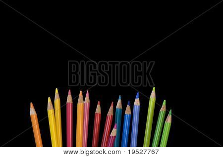 pencil crayons on black background - room for text