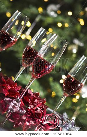 four wine glasses and red bows by christmas tree lights