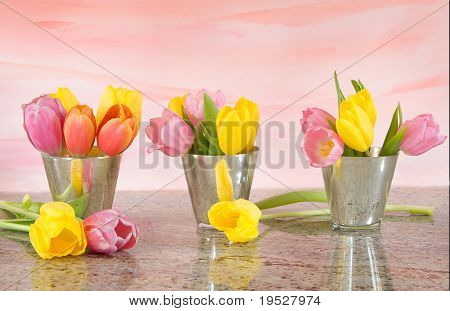 tulips in vases on pink watercolor background with granite countertop