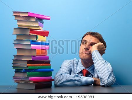man at the table looking at a stack of colored books
