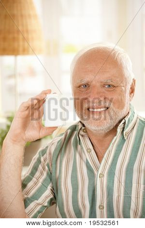 Smiling older man presenting medication, holding up phial, looking at camera, copy space.?