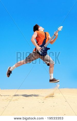 Young man with guitar  jumping on a background of blue sky