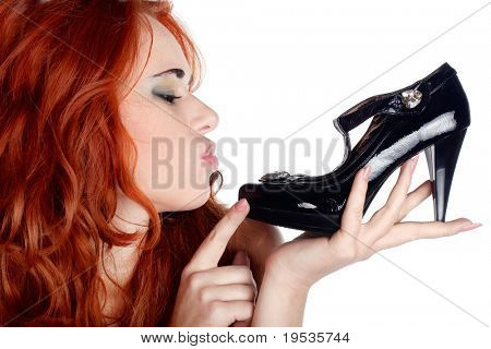 Shopping pretty girl holding a black high heel shoe in her hand and looking at it. Isolated on white background.