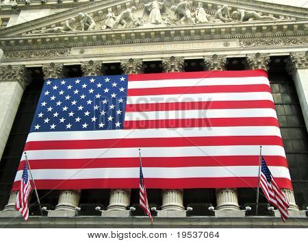 View of New York Stock Exchange facade draped with American flag. (New York City)