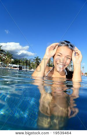 Pool woman on holidays in tropical resort swimming. Beautiful girl smiling with goggles. Asian Caucasian young woman model.