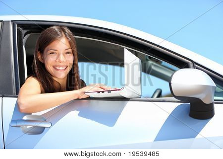 Laptop woman in car on internet outside. Smiling young woman using computer netbook outdoors. Asian Caucasian female professional.