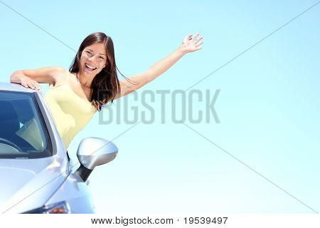 Car woman on road on road trip waving happy smiling out the window. Asian Caucasian girl on summer holidays above the clouds.