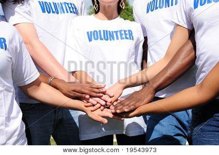 mãos do grupo de voluntários multi-étnica juntos mostrando a unidade
