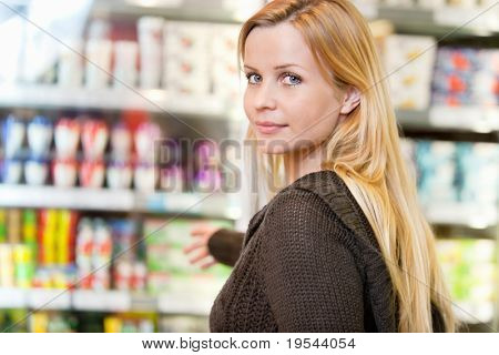 Close-up of woman reaching for products arranged in refrigerator and looking at camera