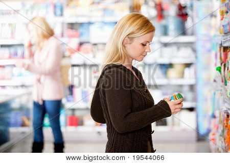 Young woman shopping in the supermarket with people in the background
