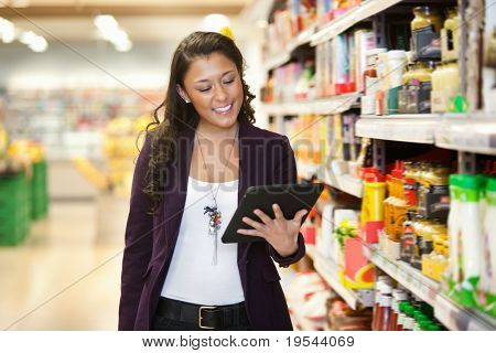 Cheerful young woman looking at digital tablet in shopping store