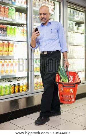 Man with shopping basket looking at cell phone while walking in shopping store