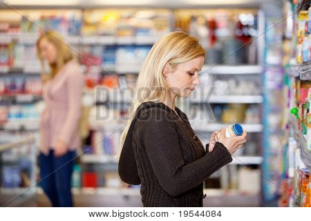 Young woman comparing products in the supermarket with people in the background