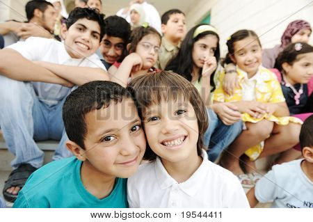Crowd of children, different ages and races in front of the school, breaktime