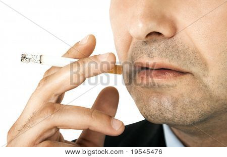 Cropped image of man holding cigarette in his hand, close-up on it and mouth
