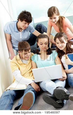 Five friends sitting in room and looking at laptop