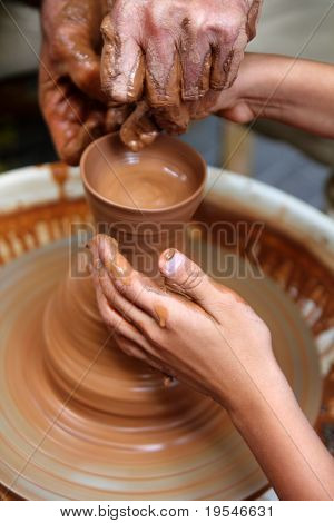 craftsman potter hands of teacher and pupil in a class clay pottery lesson