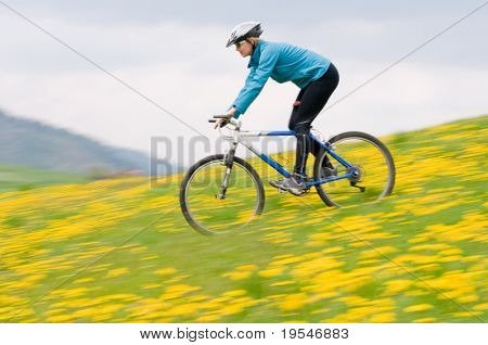 Bike riding - woman downhill on bike in dandelion  (intentional motion blur)
