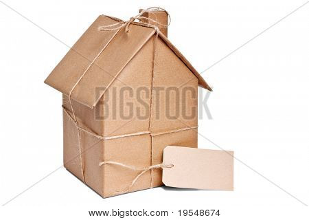 Photo of a wrapped house in brown recycled paper with label, cut out on a white background.