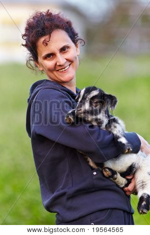 Young Woman With Baby Goat Outdoor