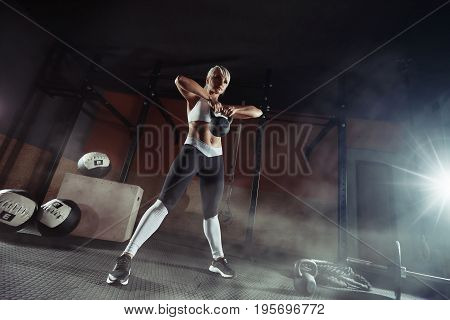poster of Fitness woman doing a weight training by lifting kettlebell. Muscular fitness woman, holds up a black kettlebell in the gym. Fitness woman in the gym. Fitness woman.