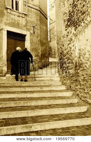 Two old Italian ladies walking up ancient steps in an Italian village