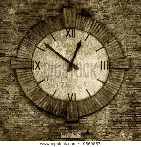 Old-fashioned clock on the side of an old brick wall, from a medieval village in europe with sepia texture.