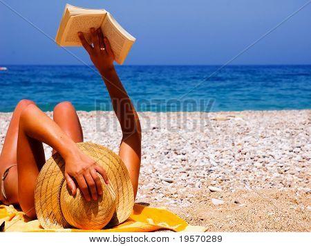Menina bonita ler romance na praia