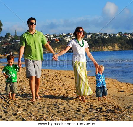 Young family having fun playing at the beach in the morning