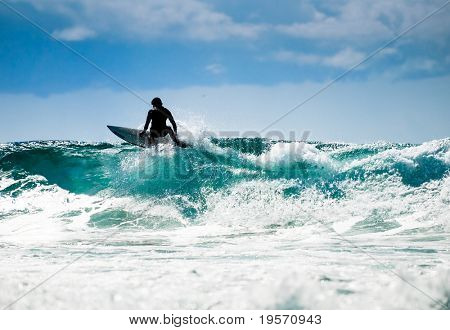 Surfing in nice  weather with great waves and blue skyline.