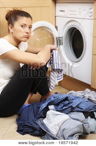 A close up of a young tired wife putting clothes into a washing machine