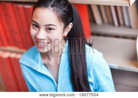 Un retrato de un estudiante asiático estudiando en la biblioteca