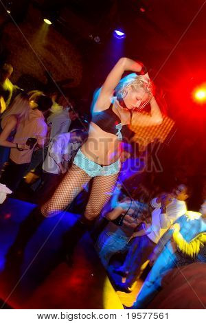 Nightclub dancer with crowd in background
