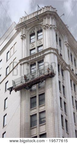 Construction workers in gondola restoring urban building facade
