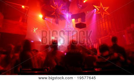 Nightclub scene with christmas decor and dance floor crowd in motion