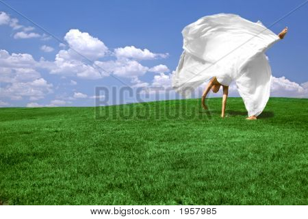 Green Grass And Blue Sky Background With Woman Tumbling