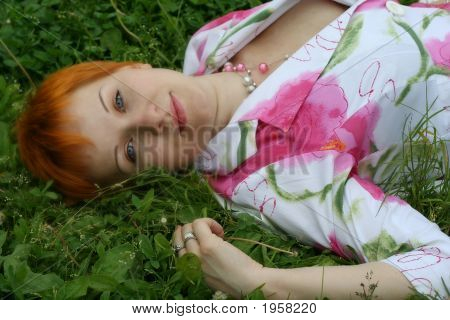 Red-Haired Girl On A Grass