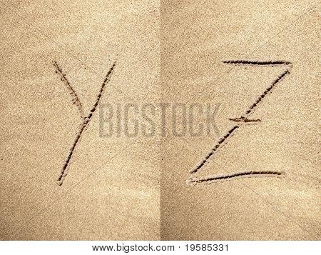 Alphabet letters Y Z handwritten in sand on a beautiful beach