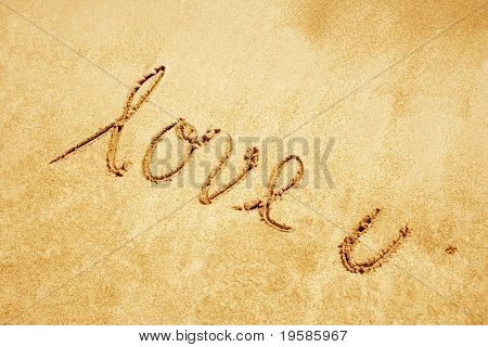 Love u handwritten in sand on a a beach