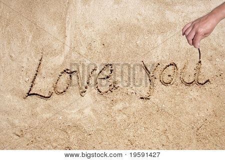 Love you handwritten in sand on a beautiful beach