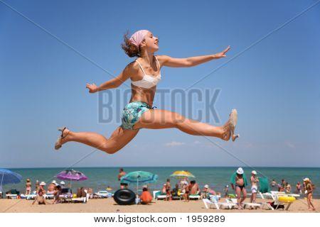Die Frau springt am Strand