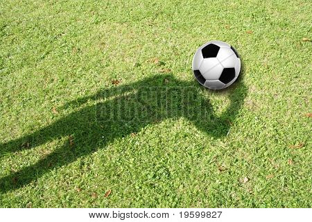 High resolution 3D soccer ball in green grass background, as the head of a human shadow. It is a conceptual background with a man standing on a field