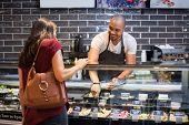 African waiter serving fresh food to young woman. Happy smiling guy preparing take away salad for wo poster
