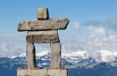 pic of eskimos  - giant rock inukshuk with mountains  - JPG