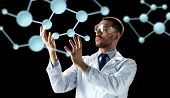 science, biology and people concept - male doctor or scientist in white coat and safety glasses with poster