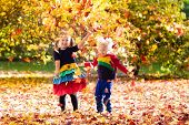 Kids Play In Autumn Park. Children In Fall. poster