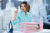 Girl Near Heap Of Rose Towels And Ironing Board poster