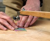 stock photo of peddlers  - Peddler using foot powered jigsaw machine to cut names - JPG